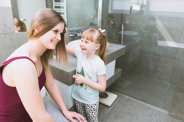 Joyeuse fille se brosser les cheveux de la mère