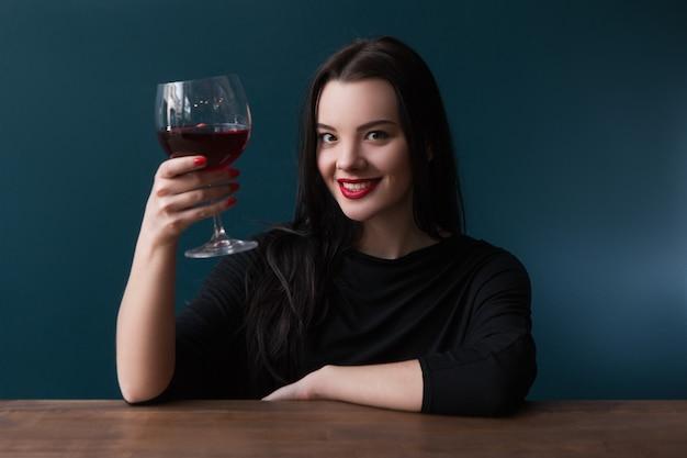 Joyeuse fille souriante au bar avec du vin. femme heureuse sur fond bleu avec espace libre, après la détente au travail. félicitations, acclamations, célébration de la fête, concept de bonheur
