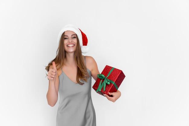 Joyeuse fille souriante et excitée du père noël tient une boîte-cadeau tandis que les gestes du pouce vers le haut font une excellente célébration