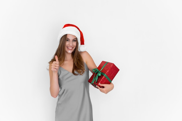 Une joyeuse fille souriante et positive du père noël tient une boîte-cadeau tandis que les gestes du pouce vers le haut font une excellente célébration
