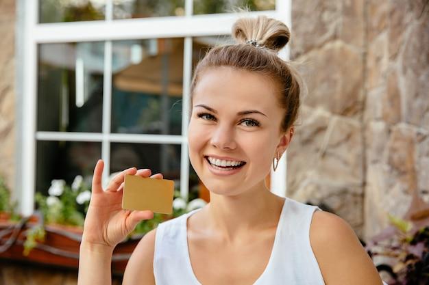 Joyeuse fille tenant une carte de crédit en or