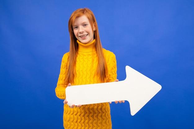 Joyeuse fille tenant un pointeur de flèche blanche à droite sur bleu