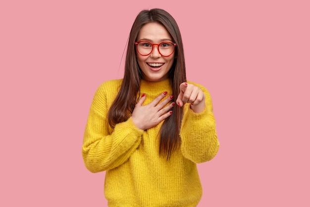 Joyeuse heureuse jeune femme métisse pointe directement à la caméra, rit avec de bonnes émotions, garde la main sur la poitrine, ne peut pas arrêter les sentiments