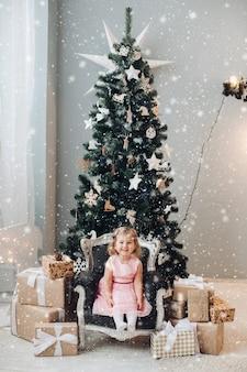 Joyeuse et heureuse petite fille souriante, assise sur une chaise antique.
