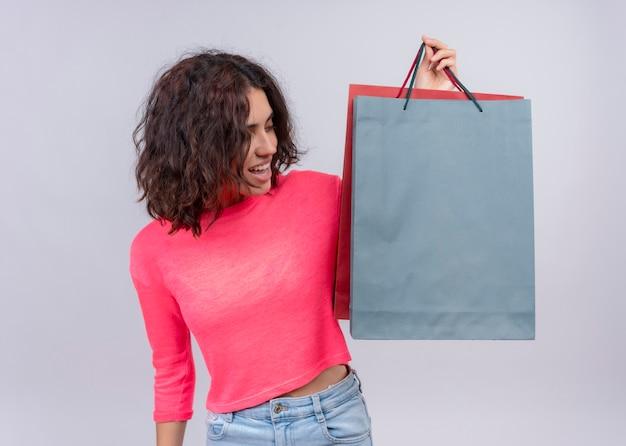 Joyeuse jeune belle femme soulevant des sacs en carton et en les regardant sur un mur blanc isolé