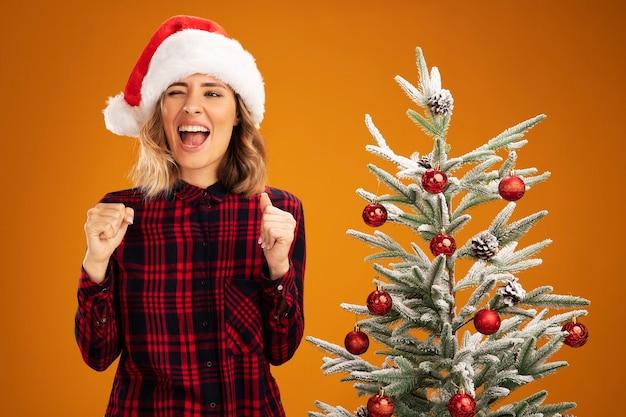 Joyeuse jeune belle fille debout à proximité de l'arbre de noël portant un chapeau de noël montrant un geste oui isolé sur fond orange