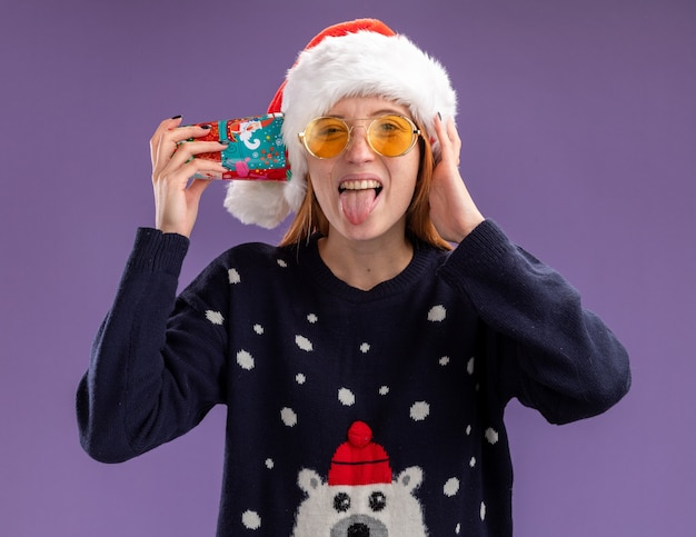 Joyeuse jeune belle fille portant un chandail de noël et un chapeau avec des lunettes tenant une tasse de noël sur l'oreille montrant la langue isolée sur fond violet