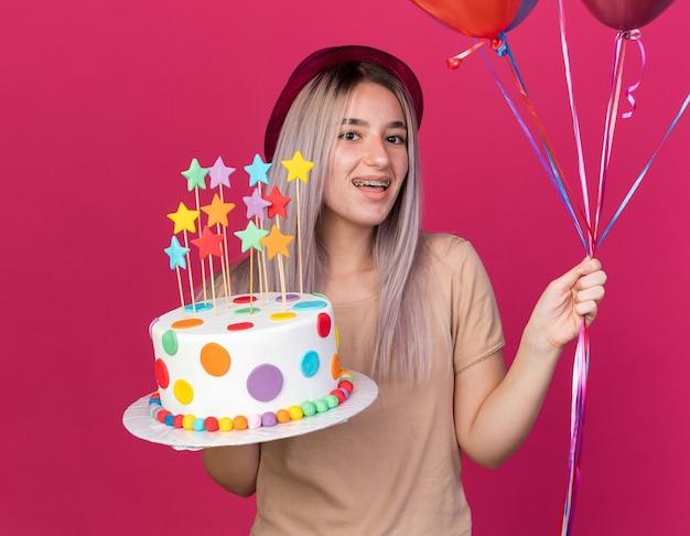 Joyeuse jeune belle fille portant un chapeau de fête avec des appareils dentaires tenant des ballons avec un gâteau