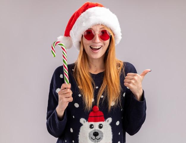 Joyeuse jeune belle fille portant un chapeau de noël et des lunettes tenant des bonbons de noël montrant le pouce vers le haut isolé sur fond blanc