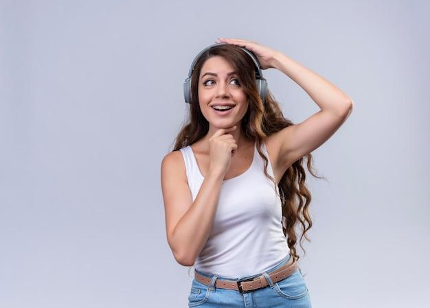 Joyeuse Jeune Belle Fille Portant Des écouteurs Mettant Les Mains Sur La Tête Et Sous Le Menton En Regardant à Droite Avec Copie Espace Photo gratuit
