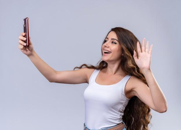 Joyeuse jeune belle fille tenant un téléphone mobile à la recherche et en agitant à elle