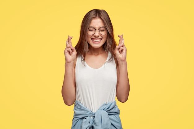 Joyeuse jeune brune avec des lunettes posant contre le mur jaune