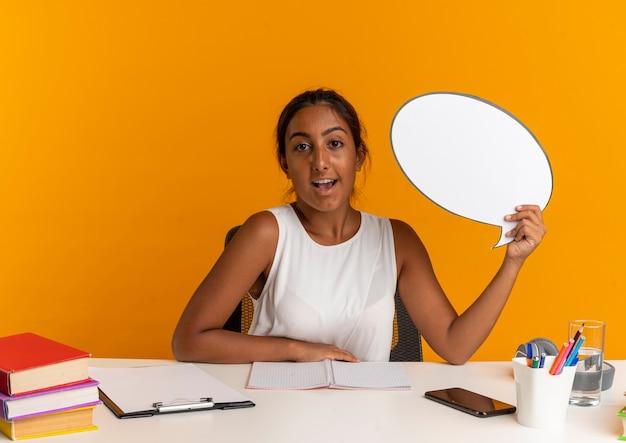 Joyeuse jeune écolière assise au bureau avec des outils scolaires tenant une bulle de discussion