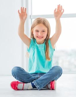 Joyeuse jeune écolière a mis ses mains en l'air alors qu'elle était assise dans la pièce dans des vêtements modernes et cool