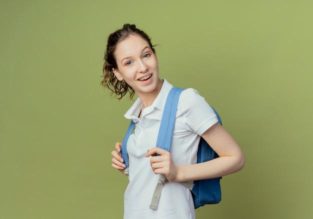 Joyeuse jeune étudiante jolie portant sac à dos debout en vue de profil tenant des sangles de sac isolé sur fond vert olive avec espace copie