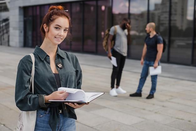 Joyeuse jeune étudiante avec livre