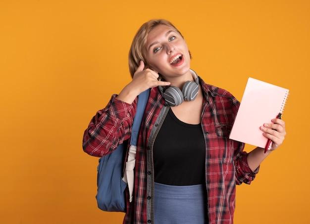 Joyeuse jeune étudiante slave avec des écouteurs portant un sac à dos tient des gestes de cahier et de stylo m'appellent signe