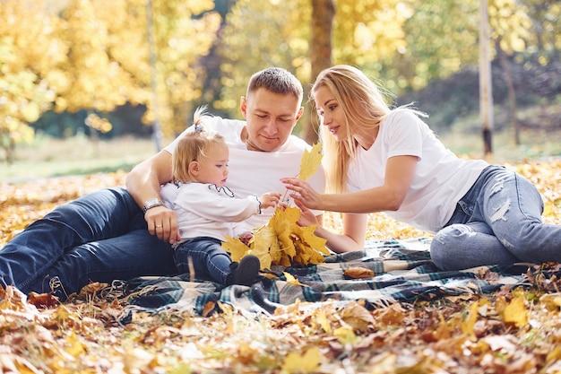 Joyeuse jeune famille allongée sur le sol et se reposer ensemble dans un parc d'automne.