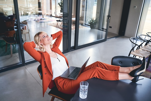 Joyeuse jeune femme d'affaires caucasienne avec ses mains derrière sa tête se relaxant au bureau