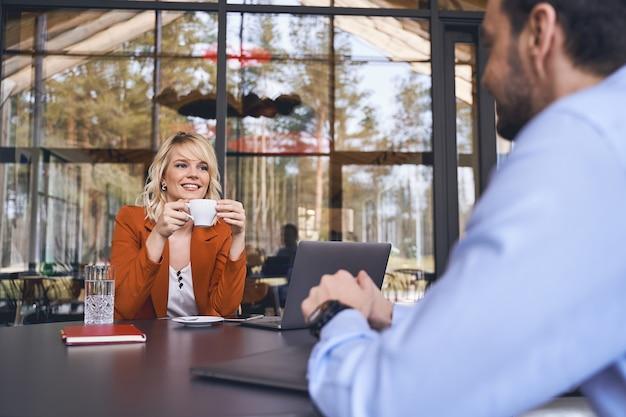 Joyeuse jeune femme d'affaires avec une tasse de thé souriant à son collègue caucasien
