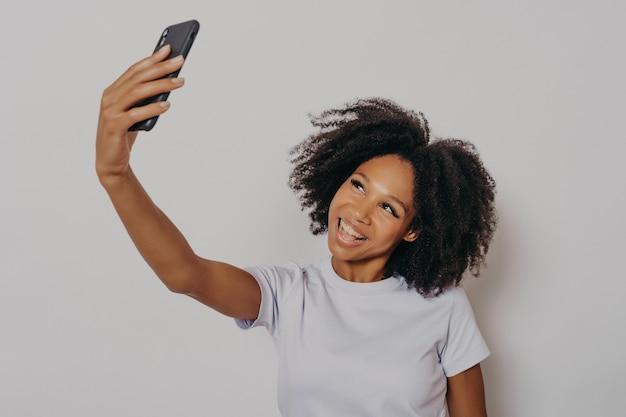 Joyeuse jeune femme africaine aux cheveux bouclés prenant un selfie sur son téléphone portable moderne, regardant la caméra souriant joyeusement tout en posant isolée sur fond de studio blanc, vêtue d'un t-shirt de base blanc