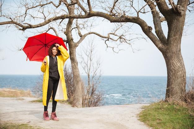Joyeuse jeune femme africaine bouclée avec parapluie marchant à l'extérieur.