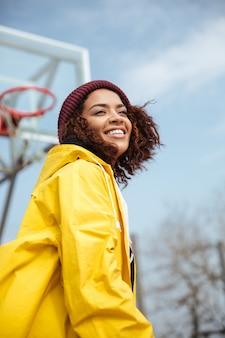 Joyeuse jeune femme africaine bouclée portant un manteau jaune