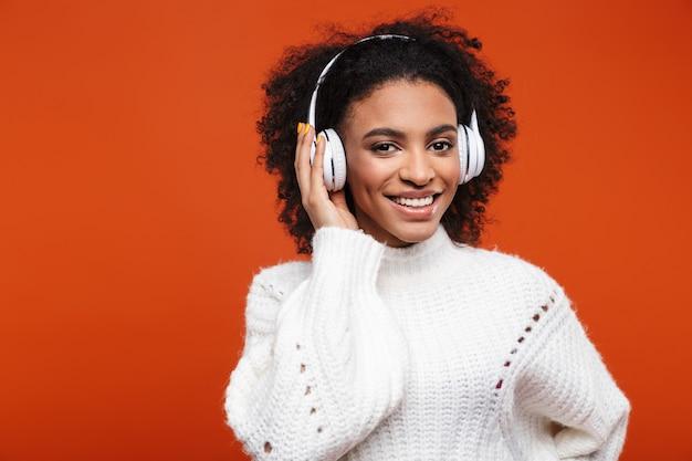 Joyeuse jeune femme africaine écoutant de la musique avec des écouteurs sans fil isolés sur un mur rouge