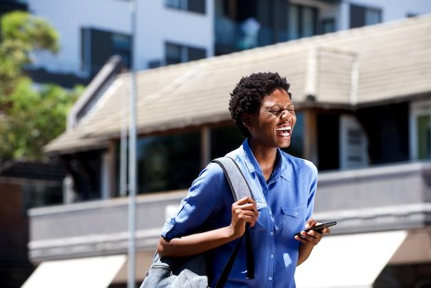 Joyeuse jeune femme africaine marchant dehors et riant avec téléphone portable