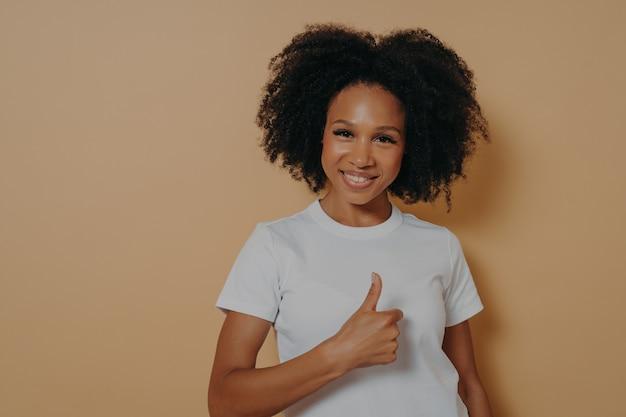 Joyeuse jeune femme africaine positive montrant un geste de réussite, le pouce vers le haut avec la main et souriant à la caméra avec une expression de visage positive, disant bien fait, isolée sur fond de studio beige
