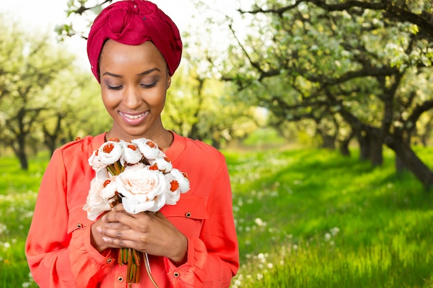 Joyeuse jeune femme africaine tenant une fleur