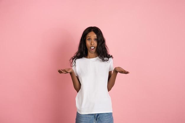 Joyeuse jeune femme afro-américaine isolée sur rose, émotionnelle et expressive