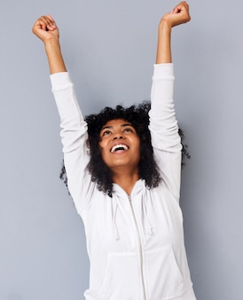 Joyeuse jeune femme afro-américaine rire avec les bras levés sur fond gris