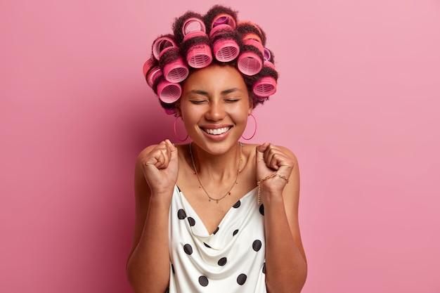 Joyeuse jeune femme afro-américaine serre les poings et célèbre quelque chose
