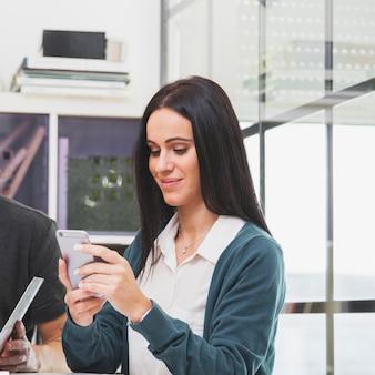 Joyeuse jeune femme à l'aide de téléphone au bureau