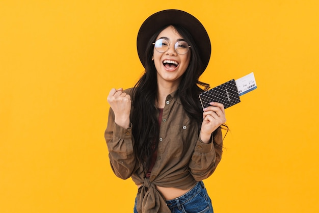 Joyeuse jeune femme asiatique montrant un passeport avec des billets d'avion isolés, célébrant