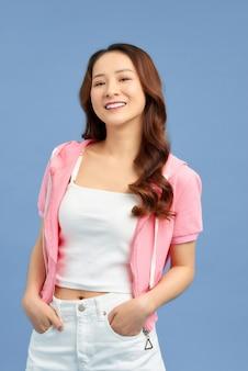 Joyeuse jeune femme asiatique portant un t-shirt blanc et un jean blanc avec une veste rose sur fond bleu coloré.