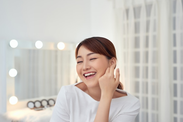 Joyeuse jeune femme asiatique touchant son visage avec une peau fraîche
