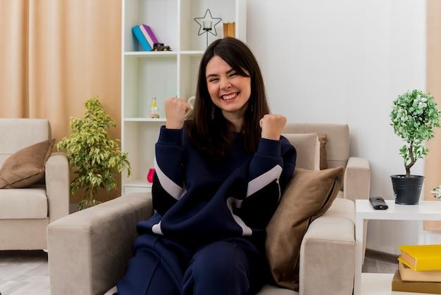 Joyeuse jeune femme assez caucasienne assise sur un fauteuil dans un salon conçu à la recherche de faire oui geste