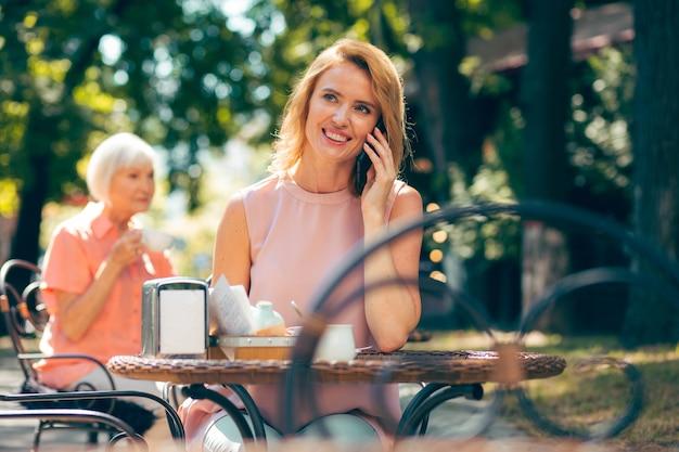 Joyeuse jeune femme assise à la table du café à l'extérieur et souriante lors d'une conversation téléphonique