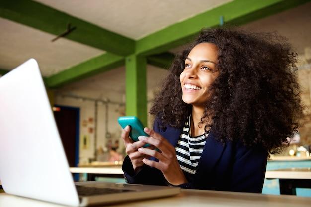 Joyeuse jeune femme au café avec téléphone portable