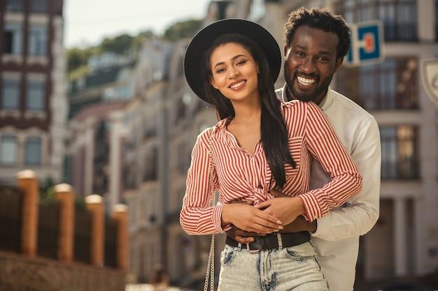 Joyeuse jeune femme au joli chapeau souriant à la caméra tandis que son petit ami heureux met les mains sur son ventre