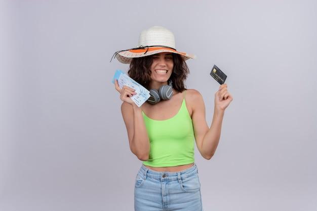 Une joyeuse jeune femme aux cheveux courts en vert crop top dans des écouteurs portant un chapeau de soleil souriant et tenant des billets d'avion et une carte de crédit sur fond blanc
