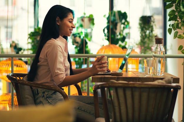 Joyeuse jeune femme aux cheveux noirs regardant l'écran de son ordinateur portable moderne avec un sourire alors qu'elle était assise dans un café avec elle