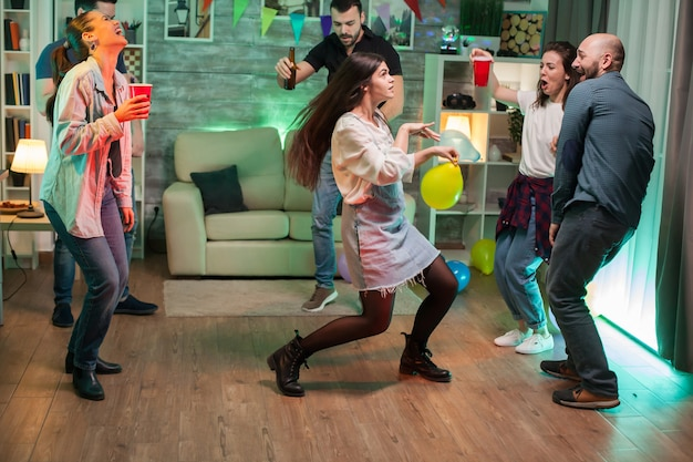 Joyeuse jeune femme avec un ballon dans les mains dansant avec ses amis lors d'une fête.