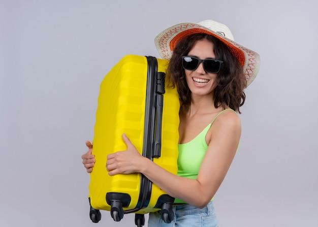 Joyeuse jeune femme belle voyageur portant chapeau et lunettes de soleil et tenant la valise sur un mur blanc isolé