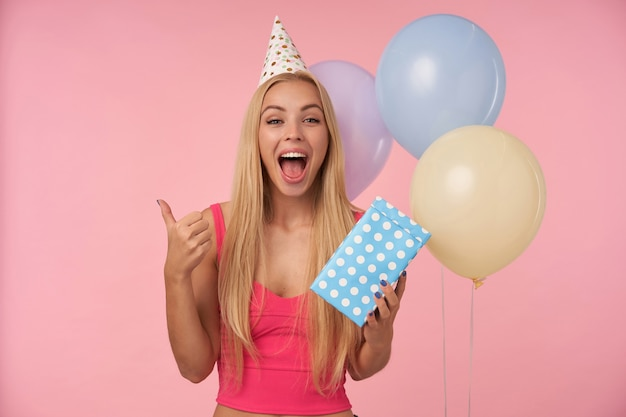 Joyeuse jeune femme blonde avec une coiffure décontractée en haut rose et chapeau de cône d'anniversaire debout sur fond rose et bouquet de ballons d'hélium multicolores, regardant la caméra et levant le pouce avec bonheur