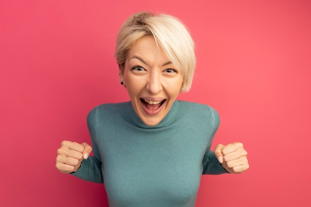 Joyeuse jeune femme blonde regardant devant faisant un geste oui isolé sur un mur rose