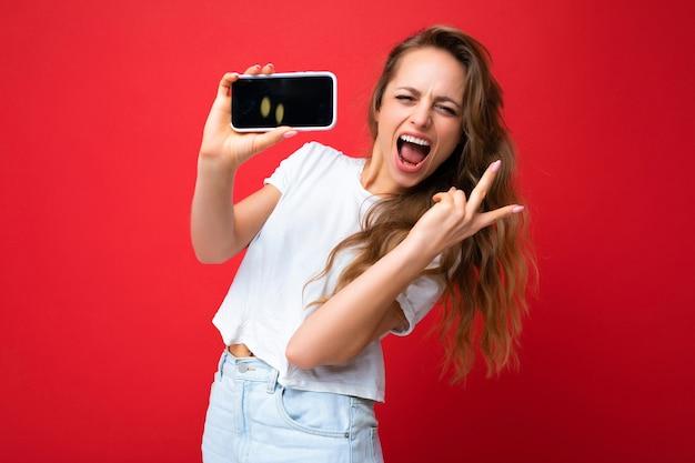 Joyeuse jeune femme blonde souriante beau portant un t-shirt blanc debout isolé sur rouge
