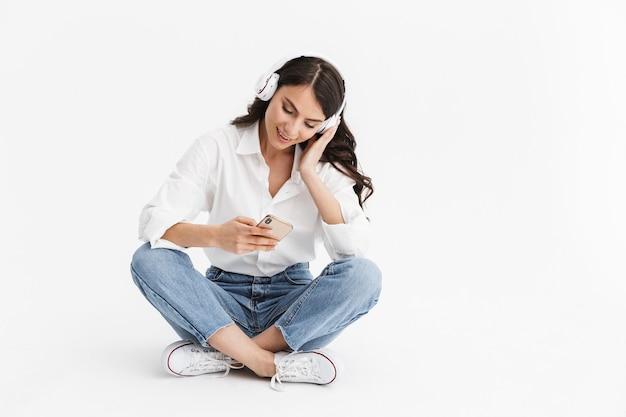 Joyeuse jeune femme brune portant une chemise assise isolée sur un mur blanc, écoutant de la musique avec des écouteurs et un téléphone portable